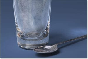 Hard water deposits on a glass and spoon